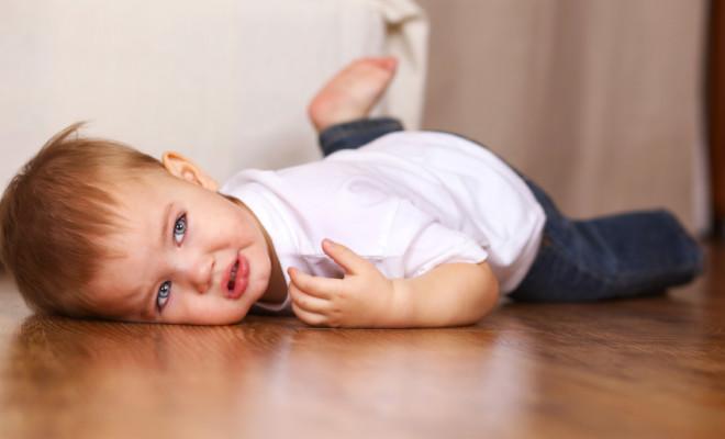 little kid crying lying on floor