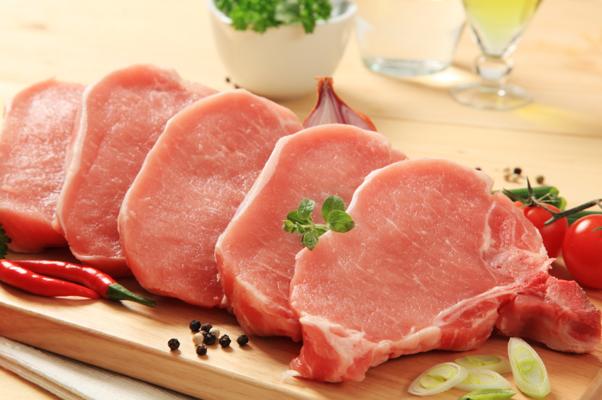 Raw pork chops on a cutting board