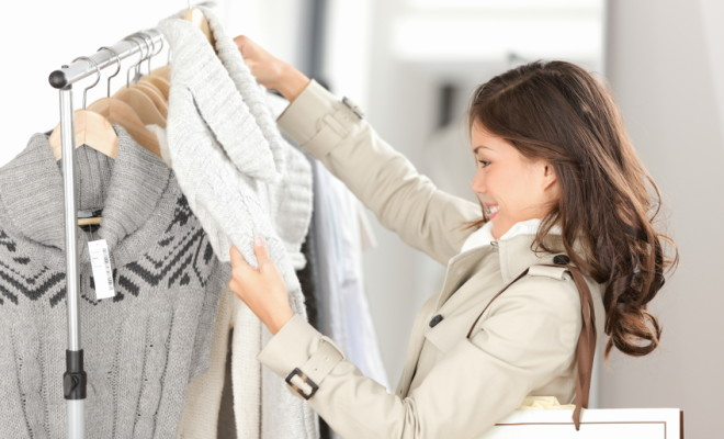 Woman shopping clothes. Shopper looking at clothing indoors in store. Beautiful happy smiling asian caucasian female model.
