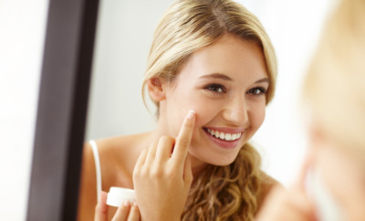 Young woman smiling while applying face cream to her skin