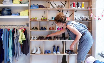 Saleswoman packing the shelves of a clothing boutique