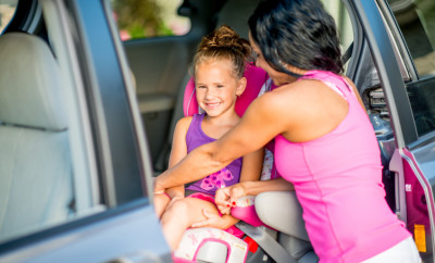 Little girl in a car booster seat.