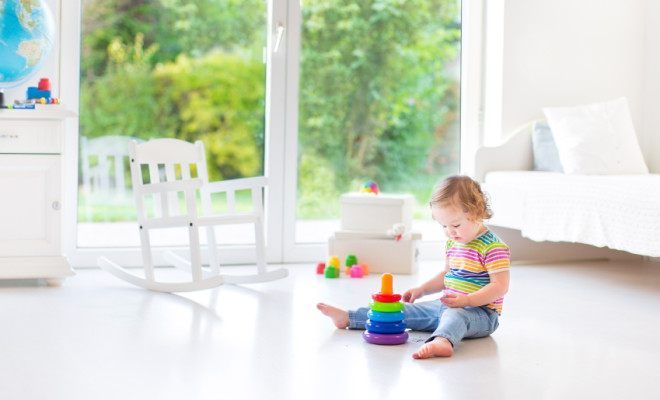 Cute toddler girl playing in a white room with big window into t