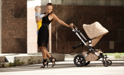 Fashionable modern mother on a city street with a pram. Young mo