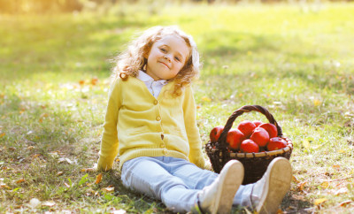 Little girl with autumn basket and apples outdoors