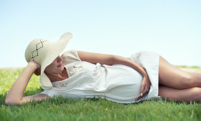 A pretty woman lying on the grass outdoors and relaxing in the sunshine