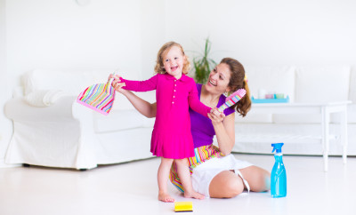 Young happy mother and her little daughter, cute toddler girl, cleaning the house together sweeping the floor in a white sunny living room with modern interion and big white couch