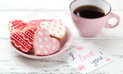 Heart cookies with cup of coffee on white wooden background