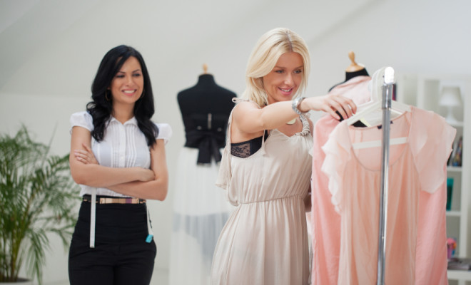 Smiling woman choosing clothes for herself at a fashion studio.