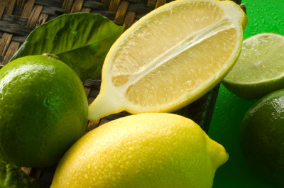 Limes and lemons with leaves and waterdrops.