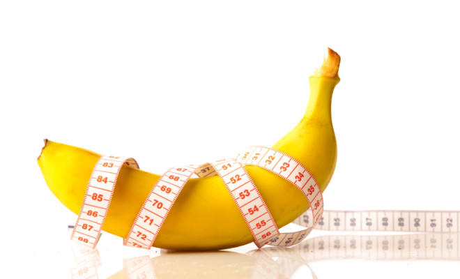 Banana with measurement tape on white background