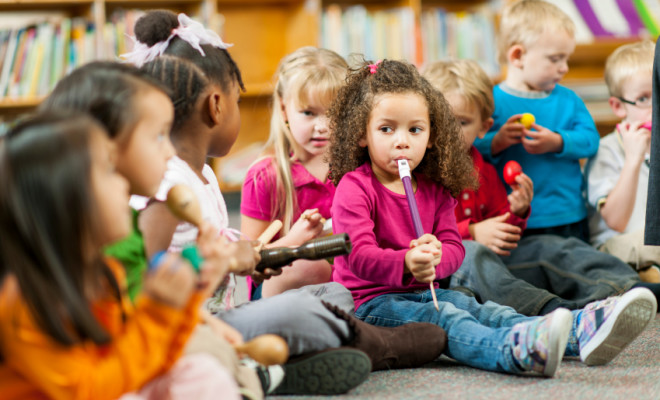 Preschool students playing musical instruments.
