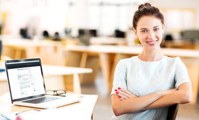 Confident Businesswoman Sitting Arms Crossed At Desk