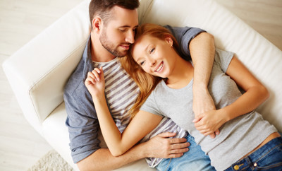 Beautiful young couple resting on sofa