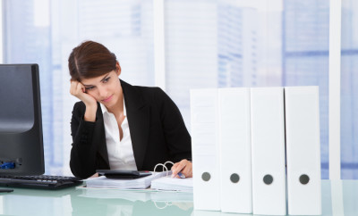 Worried businesswoman looking at binders on office desk