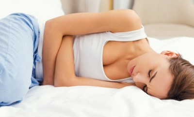 Feeling awful stomachache. Frustrated young woman holding hands on stomach and keeping eyes closed while lying in bed