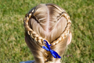 Young girl shows off her hair braided into a heart shape.
