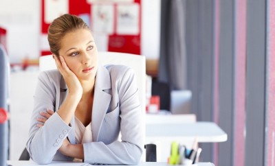Young businesswoman sits bored at her desk and looks out the window. Horizontal shot.