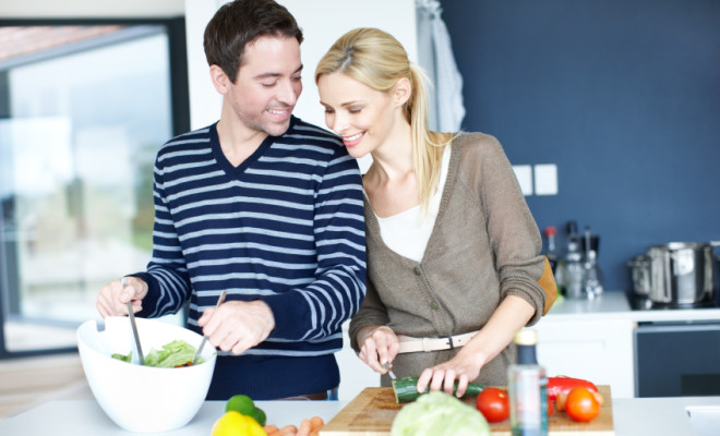 Young couple enjoying spending time in their kitchen together over the weekend