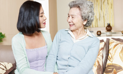 senior asian mother chatting with adult daughter at home