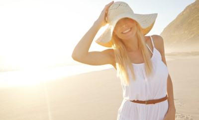 Shot of a gorgeous young woman wearing a white dress and sunhat on the beach
