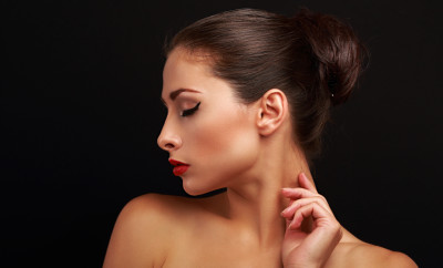 Beautiful perfect makeup model with elegant hairstyle touching health skin on black background