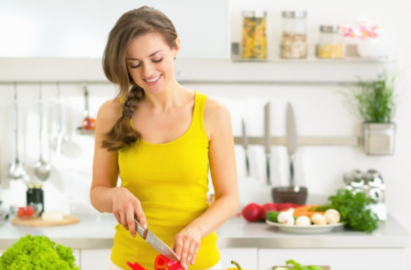 Happy young woman cutting fresh vegetables in kitchen