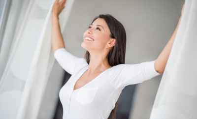 Happy woman at home opening the curtains of a window and feeling free