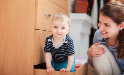 Little toddler boy playing with mom into drawer