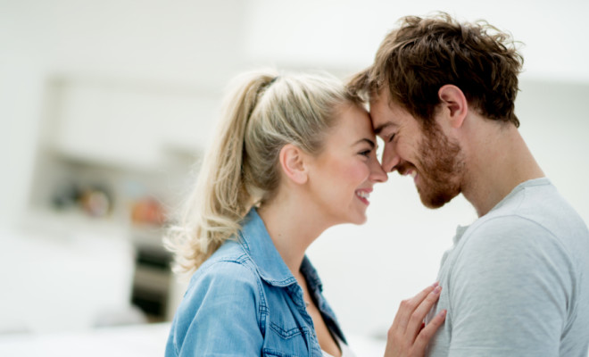 Beautiful portrait of an affectionate couple looking happy at home - relationship concepts