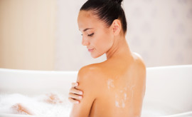 Beauty with smooth and silky skin. Rear view of attractive young woman touching her shoulder while enjoying bubble bath