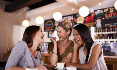 Shot of three friends having fun at a coffee shop together