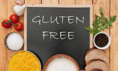 Gluten free sign handwritten on a chalk board surrounded by ingrediients