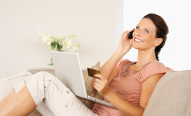 Cute mature woman shopping online using a credit card and a laptop while talking on cellphone