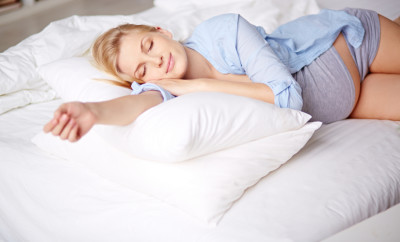 Charming pregnant beauty sleeping on bed