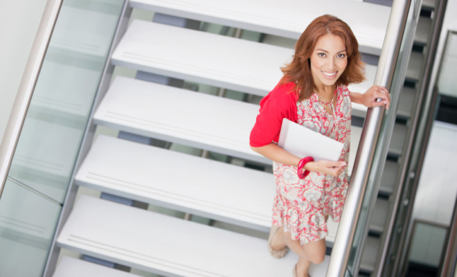 Smiling woman holding document standing on staircase at office