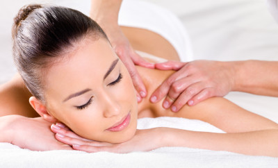 Young woman having massage on her shoulder in spa salon - horizontal