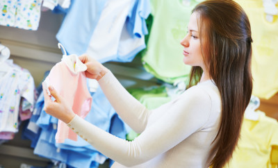 Pregnancy shopping. Young pregnant woman choosing newborn clothes at baby shop store