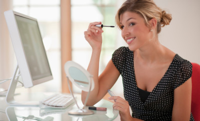Smiling businesswoman applying her mascara while at her office desk