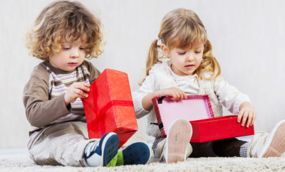 Little boy and girl opening presents.  [url=http://www.istockphoto.com/search/lightbox/9786682][img]http://dl.dropbox.com/u/40117171/children5.jpg[/img][/url]