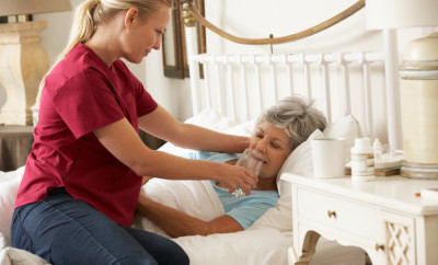Health Visitor Giving Senior Woman Glass Of Water In Bed At Home