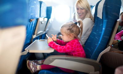 Little girl traveling by airplane with her mother and playing games on mobile phone. Focus is on foreground.