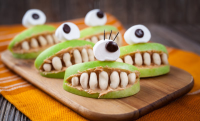 Spooky halloween edible apple monsters healthy natural dessert. Horror party decoration delicious snack. Homemade cute cyclop mouth with teeth and peanut butter on dark vintage wooden table background.