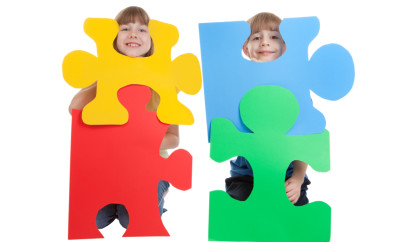 A 9 year old girl and a 7 year old boy smiling and holding colorful blank puzzle pieces.