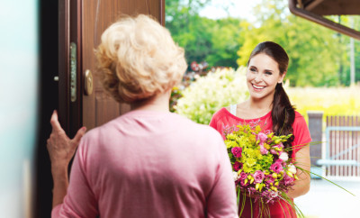Young-woman-bringing-birthday-flowers-to-her-grandmother-000050119864_Small