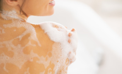 Closeup on young woman washing in bathtub. rear view