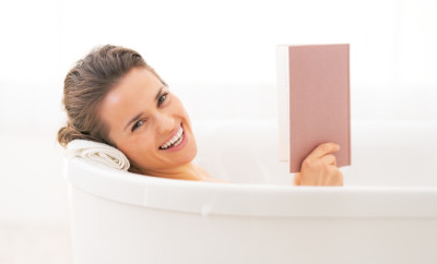 Happy young woman reading book in bathtub