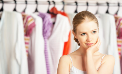 Young woman chooses clothes in the wardrobe closet at home