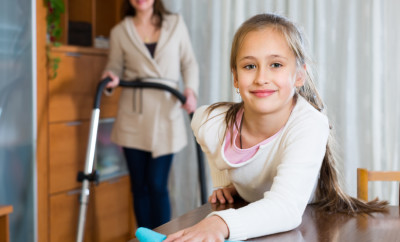Smiling little girl dusting and her mother vacuuming at home. Focus on girl