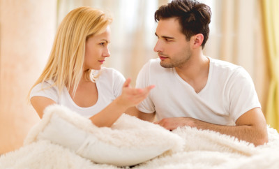 Unhappy young couple sitting in bed and having conflict.